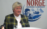 Elisabeth Aspaker, Norway's fisheries minister, in front of the Norwegian seafood export logo